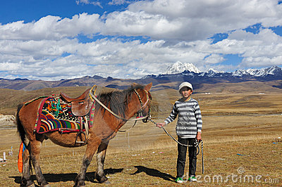 Tibetan kid pulling horse Editorial Image