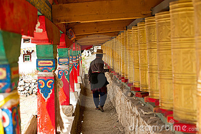 Tibetan man walking through corridor with prayer w Editorial Stock Image