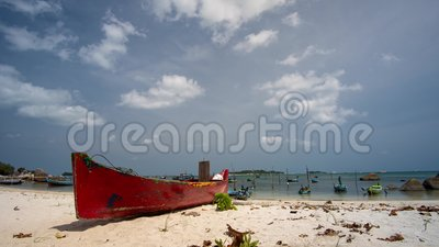 Tiempos de hermosas nubes en la isla tropical de Belitung Indonesia - Tanjung Kelayang con un pequeño bote de madera como frente almacen de metraje de vídeo