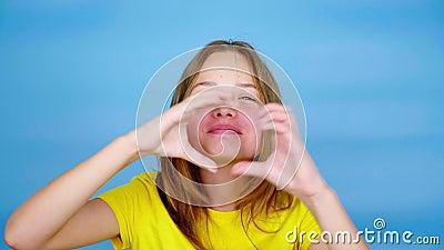 Tien meisje in een geel T-shirt kijkt naar camera, blaast een kus en toont hartvorm