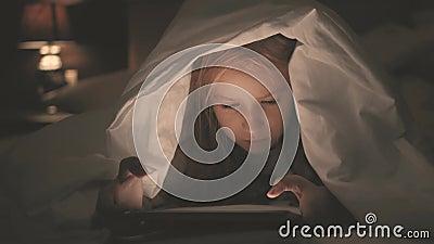 Tiener die in bed een tablet in sociaal Internet in het donkere licht spelen Sluit omhoog van meisje het letten op video op stock videobeelden