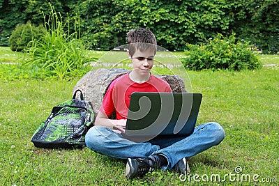 Tiener met laptop in het park
