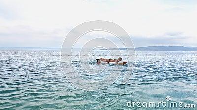 Tienermeisjes die plezier hebben met opblaasbare matras in blauwe zee stock footage