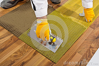 tile adhesive with trowel on wooden floor