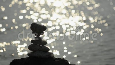 Tiled rocks silhouette with sun sparkles in water behind stock footage