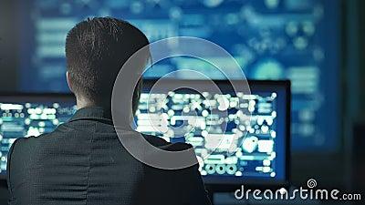 Tillbaka sikt av programmerare som arbetar på datoren i mörkt digitalt kontor arkivfilmer
