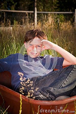 Tillfällig ung pojke i en skottkärra