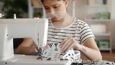Tilt up video of woman sewing protective masks on the machine stock footage