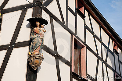 Timber framing house with religious statue
