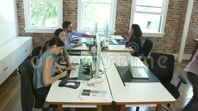 Time Lapse Sequence Of Workers At Desks In Design Office. Speeded up sequence showing office workers sitting at desks,using computer,meeting with colleagues and stock video