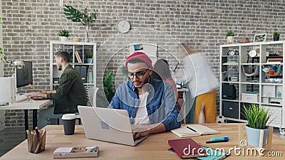 Time lapse van de jonge mens die met laptop in bureau werken terwijl zich collega's het bewegen stock videobeelden