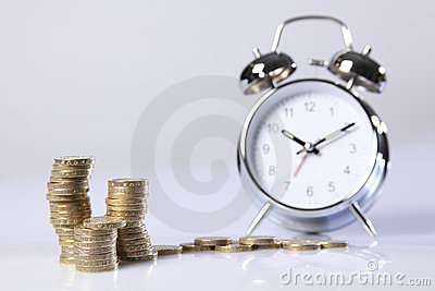 Time is money silver alarm clock and pound coins