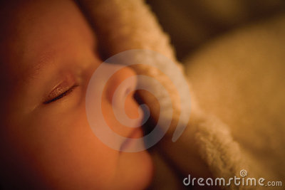Tiny baby asleep in furry baby grow