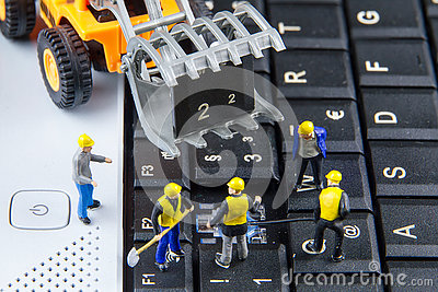Tiny toys team of engineers repairing keyboard computer laptop.C Stock Photo