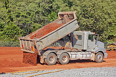 Tip truck dumping dirt on a construction site