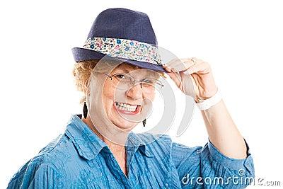 Tippar den gulliga en mitt åldrades kvinnan hatten