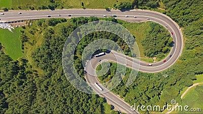 Tir aérien étonnant du trafic de voiture sur la route de serpentine de forêt clips vidéos