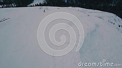 Tir d'un hélicoptère au-dessus de la piste de la station de ski avec des sportifs actifs tir d'avion banque de vidéos