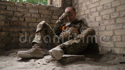 Tired after battle army soldier sitting on ground. Tired after battle army soldier taking helmet off while sitting on the ground and leaning on wall in the stock video