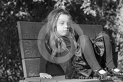Tired Or Bored Little Girl Sitting On A Bench Stock Photo