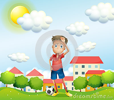 A tired boy standing with a soccer ball