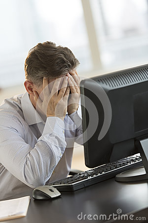 Tired Businessman Leaning On Computer Desk