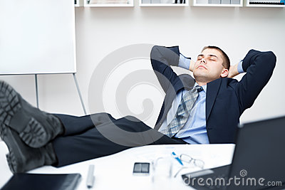 Tired businessman sleeping on chair in office