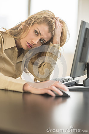 Tired Businesswoman Looking Away While Sitting At Computer Desk
