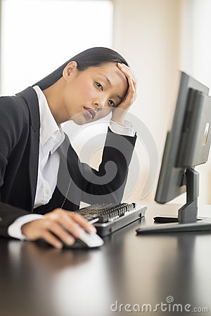 Tired Businesswoman Using Computer At Desk