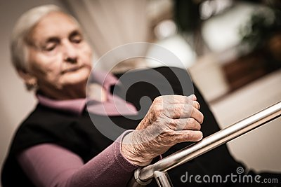 Tired elderly woman - focus on hand Stock Photo