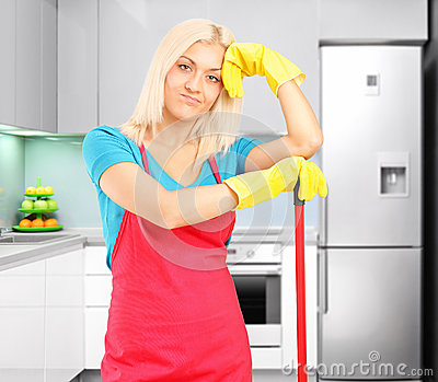 Tired female cleaner after cleaning a kitchen