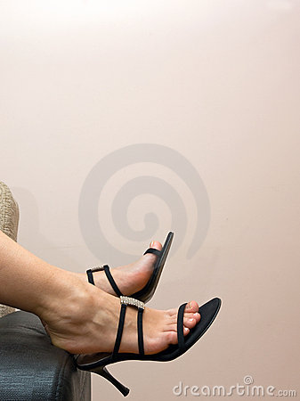 Tired female feet in sandals over a couch