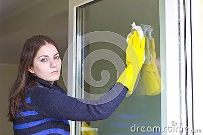 Tired girl washing windows at home Stock Photo