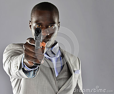 Man in a suit aims his firearm at the viewer