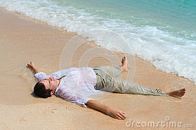 Tired man lie on sandy beach