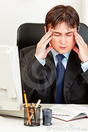 Tired modern businessman sitting at office desk
