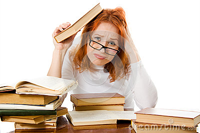 Tired red-haired girl in glasses with books