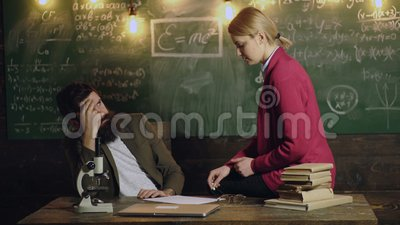 Tired teacher and female student sitting on the table communicate and solve  problems  Contemplative young professor and