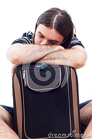 Tired traveler tourist man sleeping on luggage