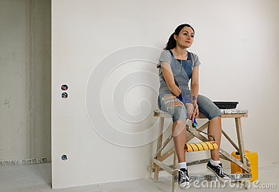 Tired woman relaxing while painting a wall