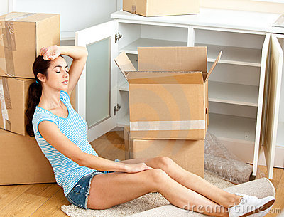 Tired woman sitting on the floor after unpacking