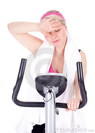 Tired woman on stationary bicycle