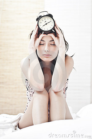 Tired woman with thealarm  clock