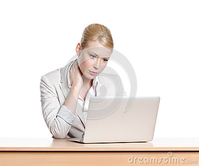 Tired young businesswoman sitting at a office desk with laptop