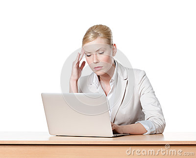 Tired young businesswoman sitting at a table with laptop