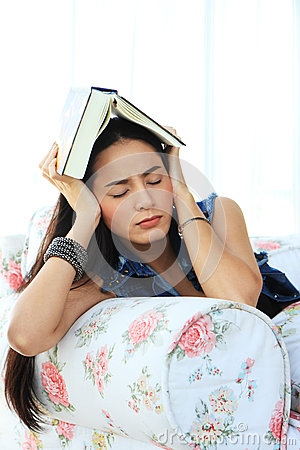 Tired young woman taking a nap at home lying on sofa with a book