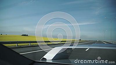 Tiro aéreo de Grey Car Driving en el camino al lado del campo de flores y de tierras de labrantío amarillas metrajes