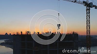 Tiro aéreo del emplazamiento de la obra con las grúas y los trabajadores en la puesta del sol metrajes