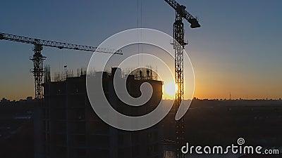 Tiro aéreo do canteiro de obras com guindastes e trabalhadores no por do sol filme