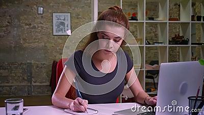 Tiro de trabalhar a fêmea ruivo caucasiano, concentrado em seu trabalho, sentando e fazendo as anotações, verificando video estoque